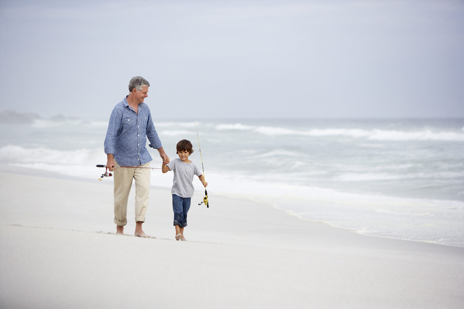 Grandfather & boy fishing on beach